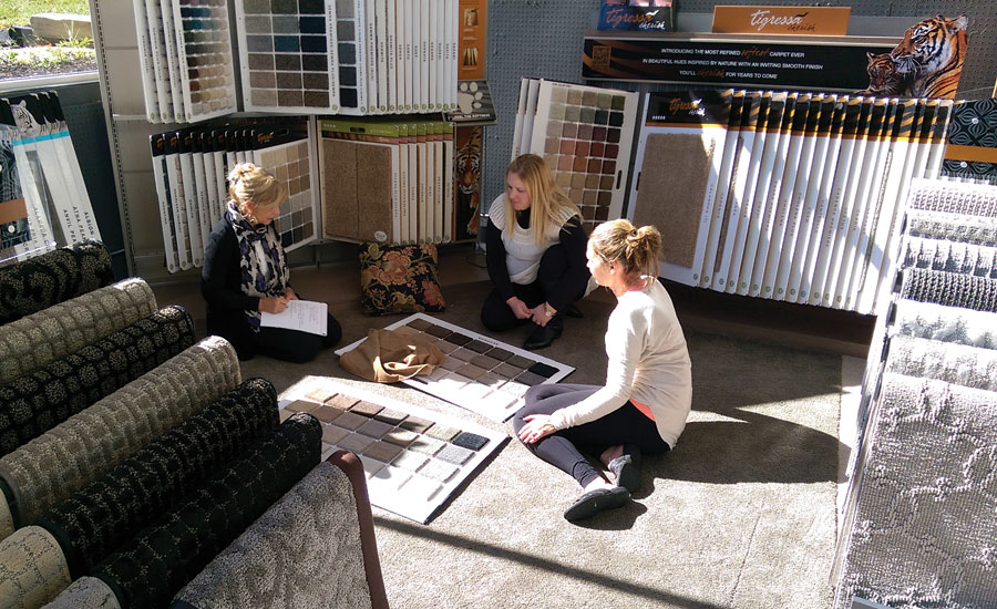 Designer, retail employee discuss carpet options with customer